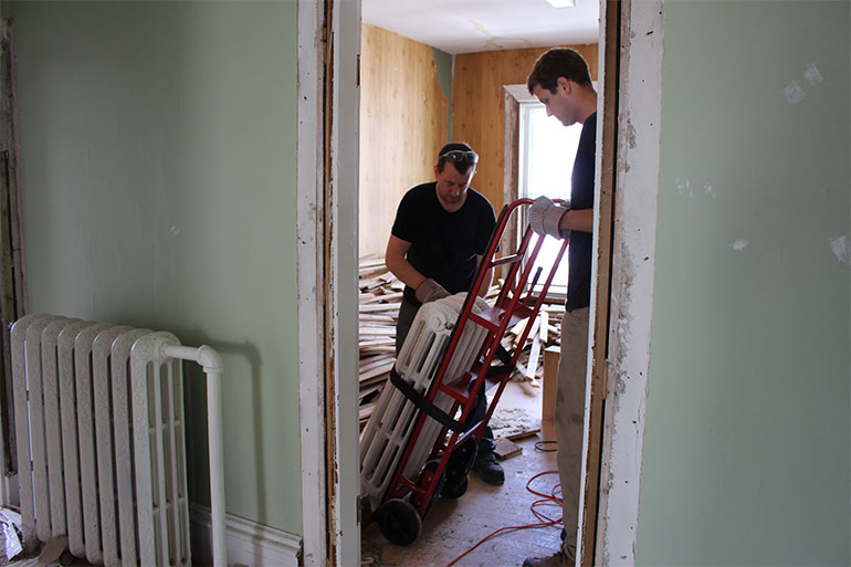 Kevin and Alex remove one of the heavy iron radiators. The radiators will be reused in another project.