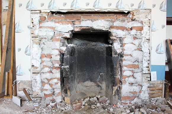 Work ongoing. The surrounding face and mantle from a downstairs room fireplace have been removed.