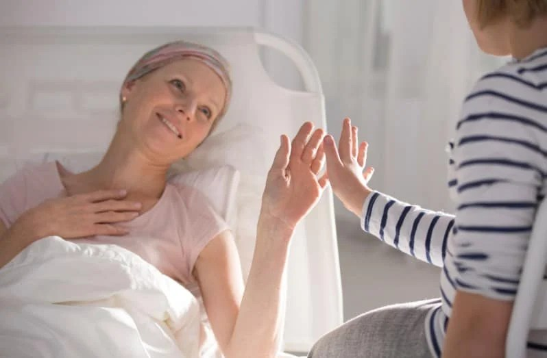 Daughter about to touch hands with mother who is on hospice