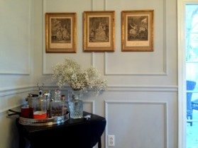 3 French vintage prints hang on the trim.