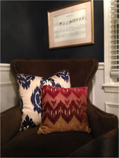 A blue Ikat throw pillow, trimmed/corded in leopard, is paired with a pink and red toned tribal pillow.