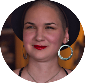 Karina, a woman with shaved hair is wearing a black hat and large silver earrings.