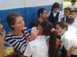 A volunteer paints faces during a dynamic activity at one of the schools.