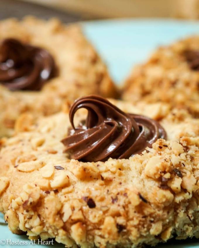 Nutella Filled Hazelnut Thumbprint cookies are quick and easy cookie to make. The exterior is crunchy with a hazelnut roasted exterior, a soft cookie interior, and then topped with a creamy hazelnut flavored chocolate topping called Nutella - Hostess At Heart