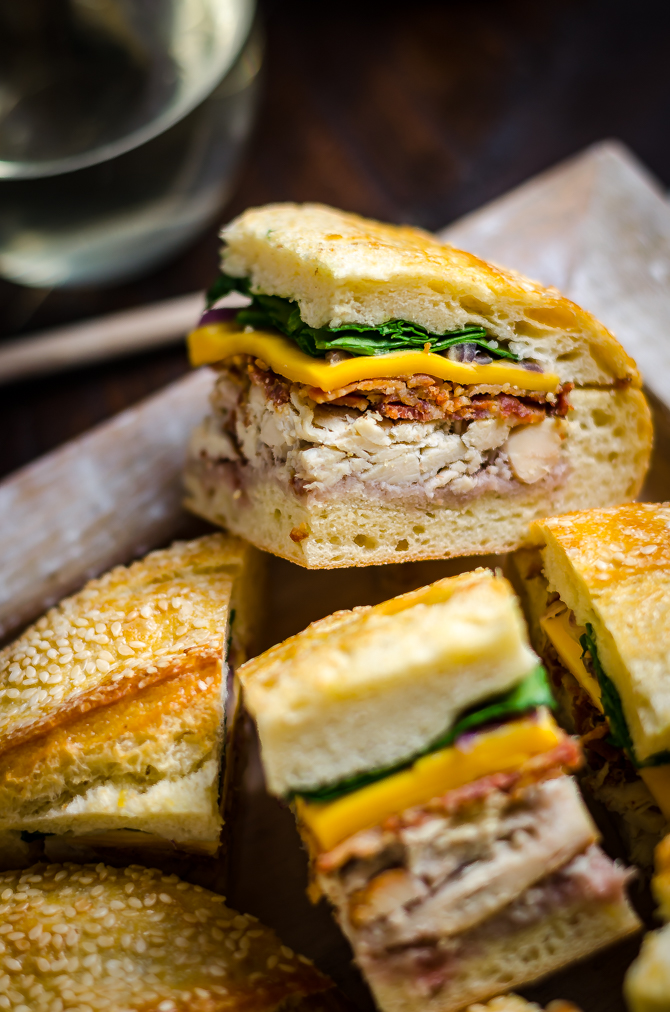Chicken Bacon Pressed Picnic Sandwiches with Raspberry Honey Mustard. These tangy smash-hit sandwiches are great for potlucks, barbecues, picnics, parties, and all that lies in-between. With a raspberry honey mustard, chicken, bacon, cheddar cheese, red onion, and baby spinach filling, they are always devoured. Plus, you can easily make them ahead of time and transport them with no stress! | hostthetoast.com