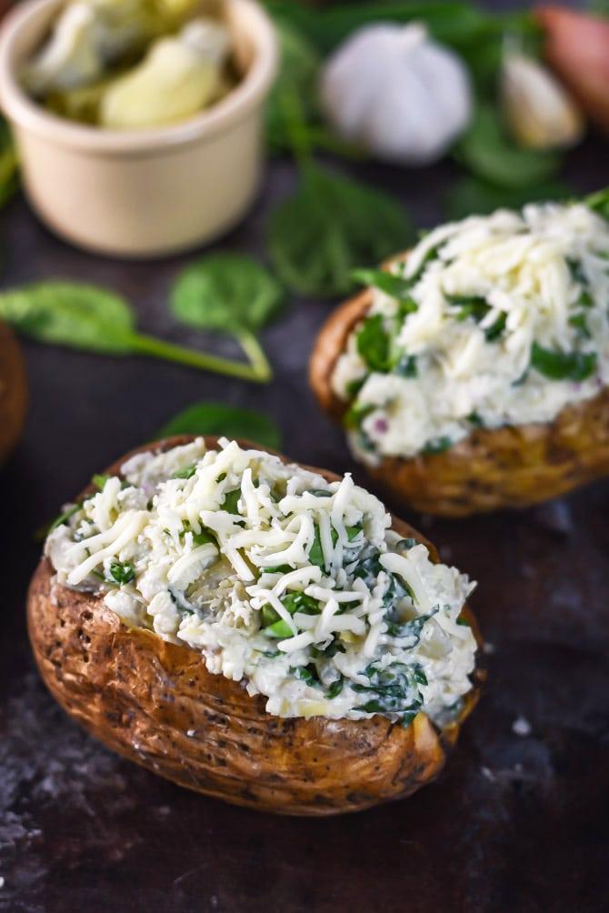 Spinach and Artichoke Dip Baked Potatoes. Hearty baked potatoes with a creamy, cheesy spinach and artichoke dip filling.   hostthetoast.com