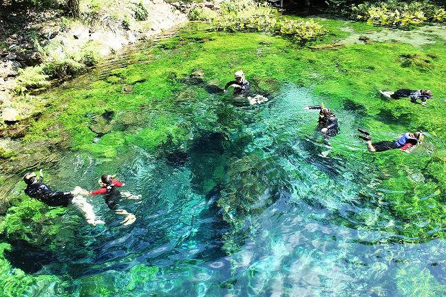 Mergulhadores em lago nascente azul