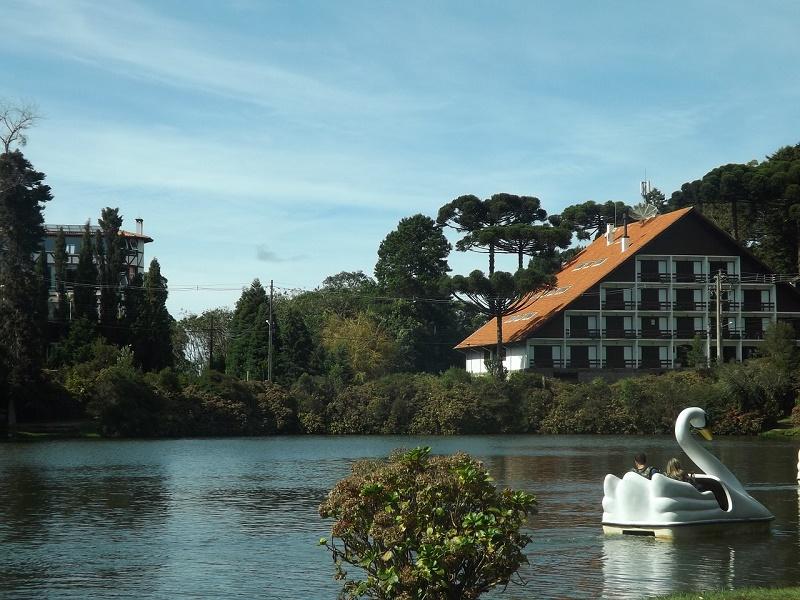 imagem-de-lago-com-pedalinho-em-frente-a-floresta-com-hotel