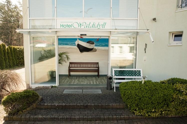 Der Eingangsbereich vom Hotel Waldidyll GmbH Zinnowitz mit großem Gemälde von einem Schiff am Strand.