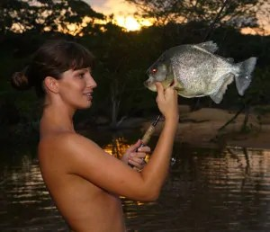Topless girl holding up a fish