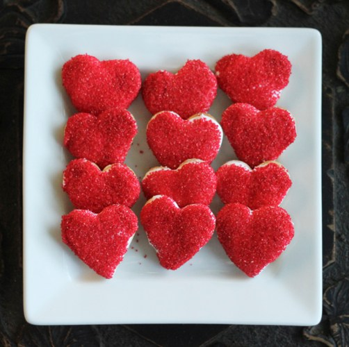 Heart-shaped biscuits covered in white icing then red sprinkles