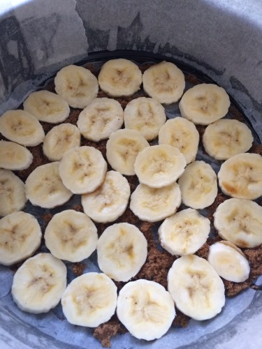 Spreading the sliced bananas across the bottom of the cake tin