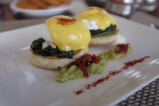 Eggs benedict with crab meat and avocado on the side.