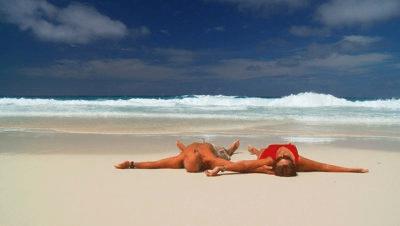 people lying on beach travel buddies