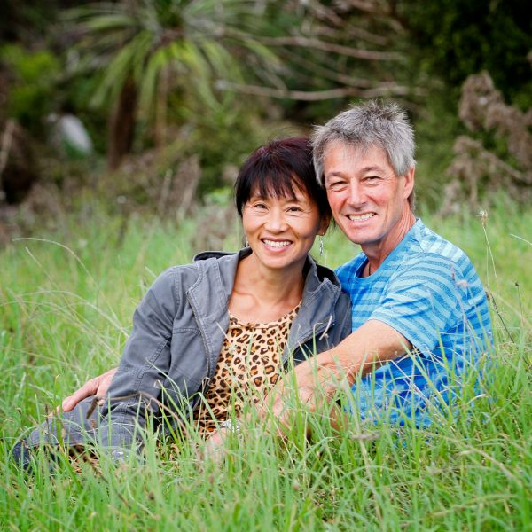 wedding portrait commercial photographers Martin and Rebecca in the grass at Tawharanui Beach regional park, Auckland new Zealand