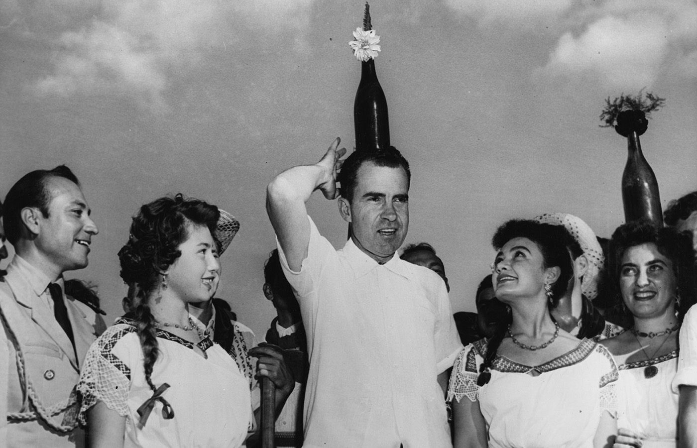 Richard Nixon balances a bottle on his head