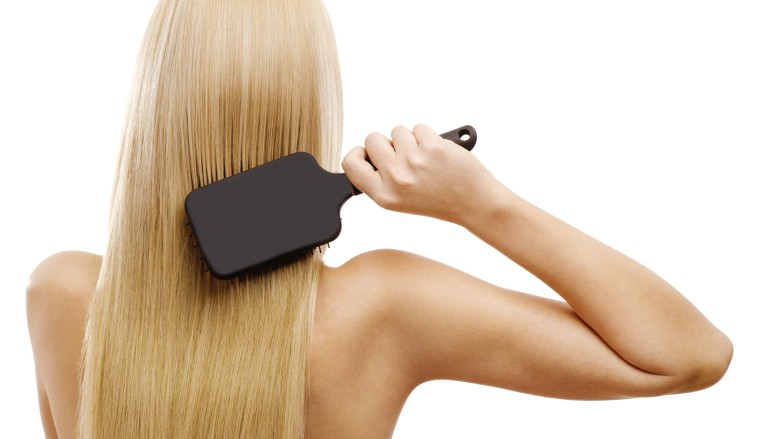 women brushing tape in extensions