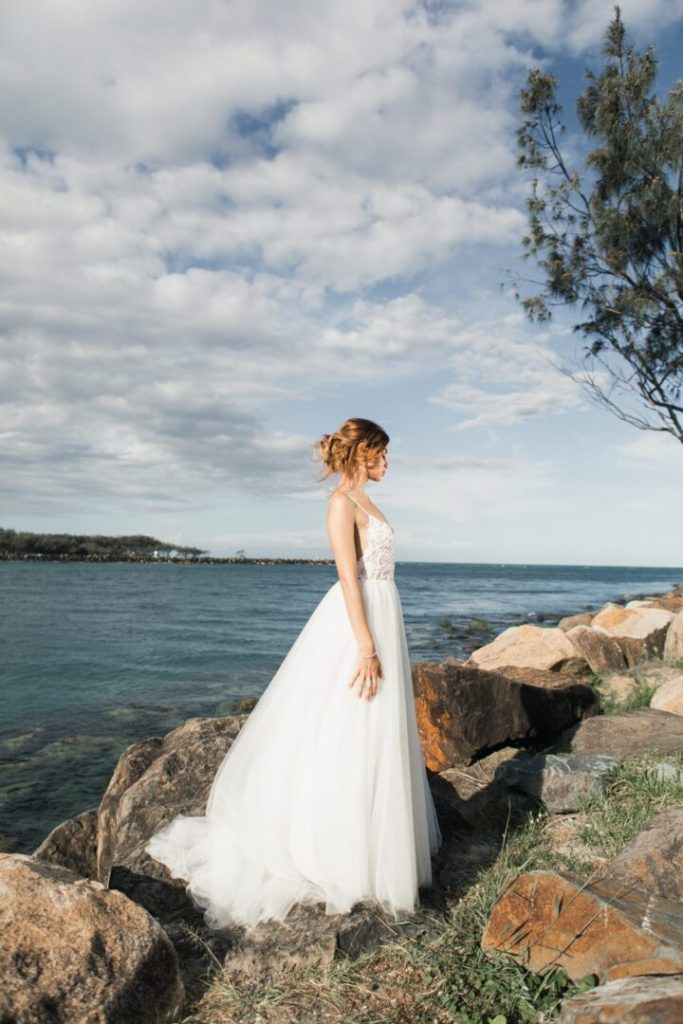 bride standing on rocks wearing white wedding dress with hair in beautiful updo