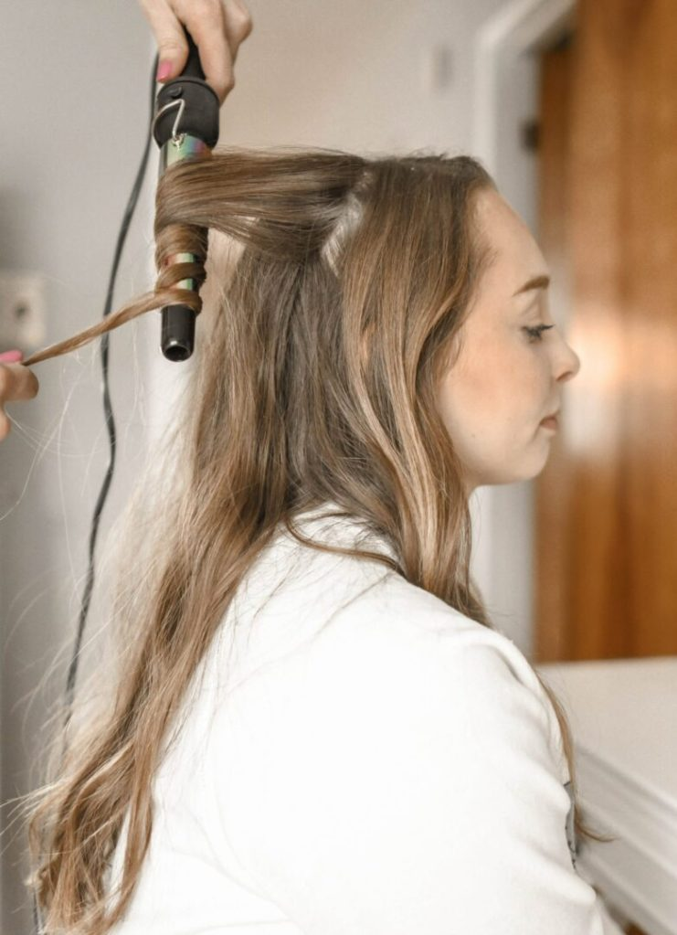 woman curling-her hair extensions with a wand