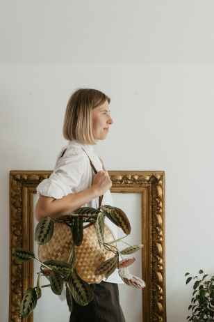 woman holding bag standing near wall