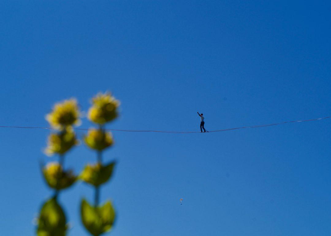 Un funambule sur une slack line à plusieurs dizaines de mètres au dessus du sol à la Grande Ballade sur le Semnoz