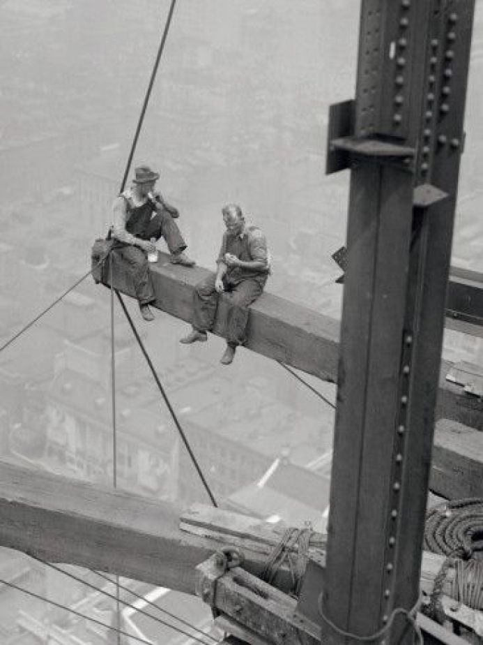 old photo of workers sitting on a beam