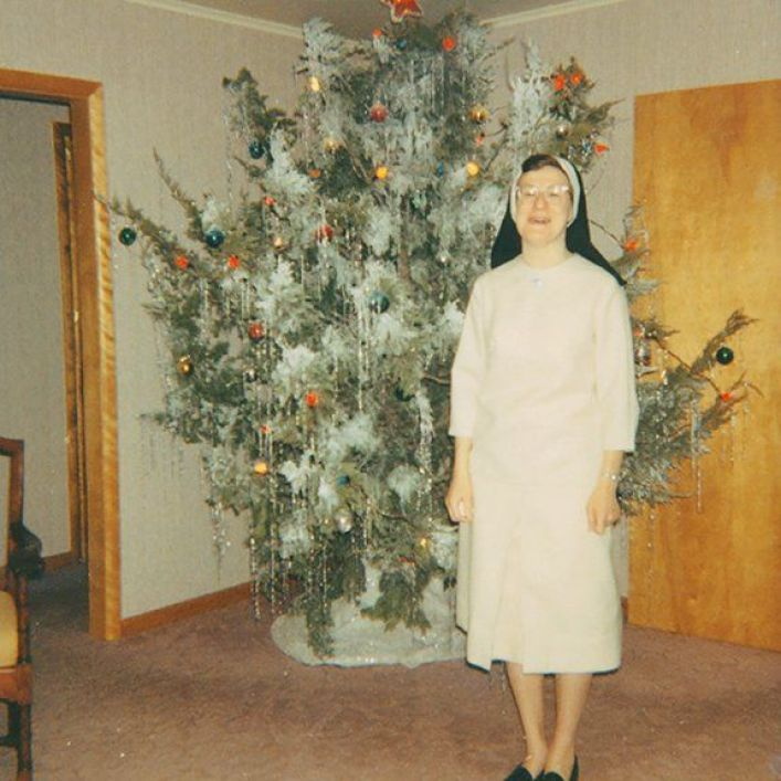 Nun in front of Christmas tree