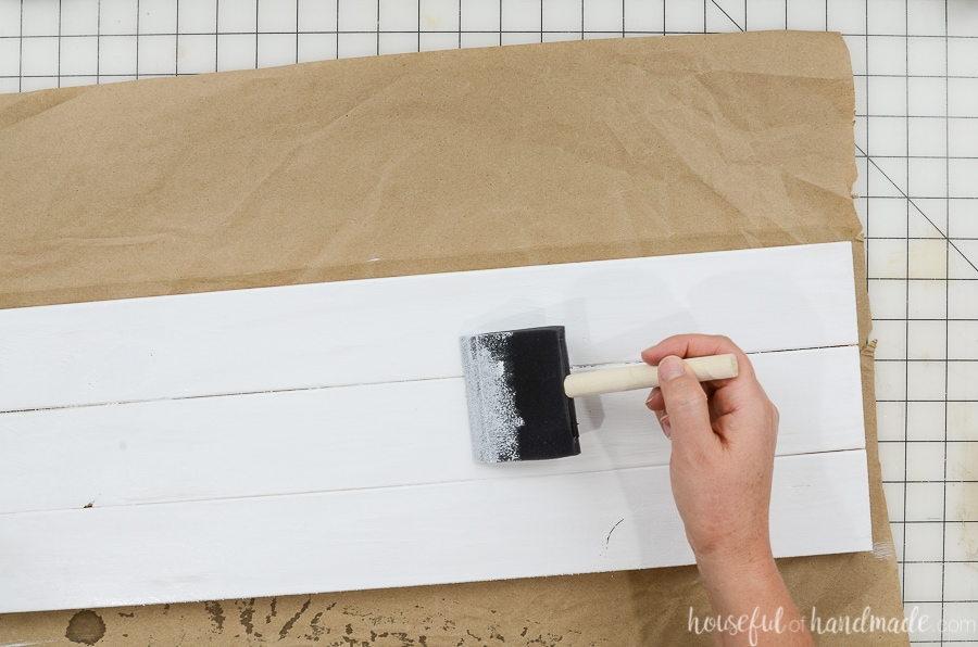 Painting one side of the wood sign white with a foam brush.