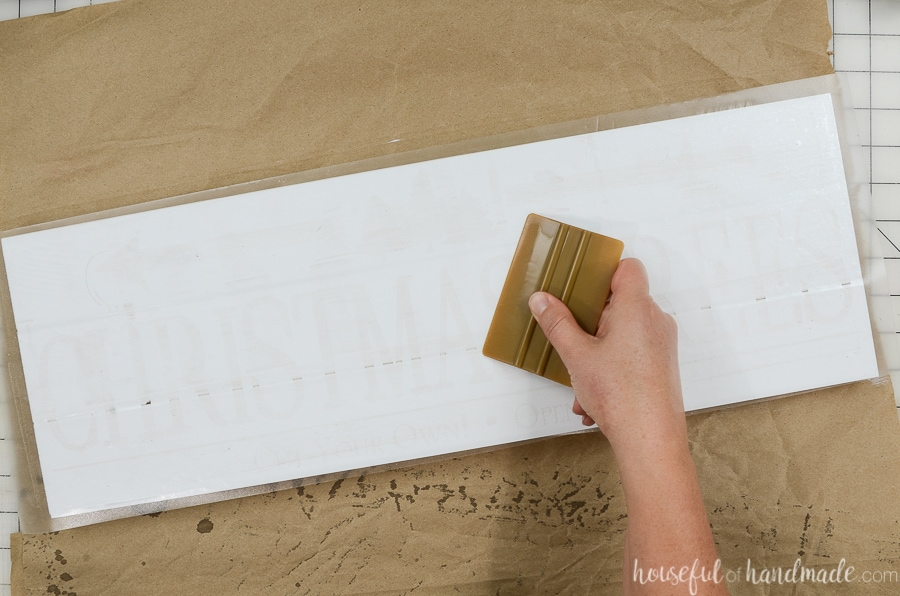 Using a vinyl scrapper to smooth the vinyl stencil over the white painted wood boards.