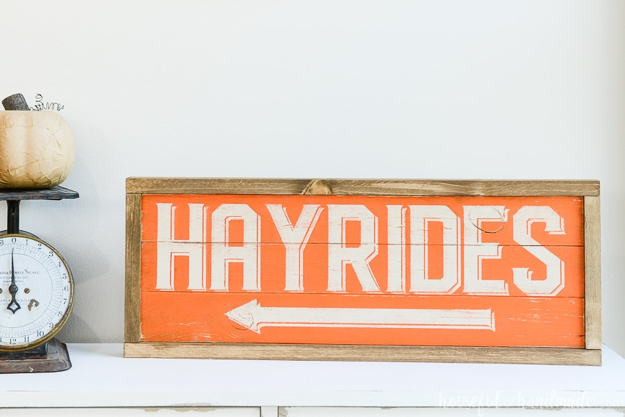 Orange and cream hayride wood sign with stained frame on a console table.