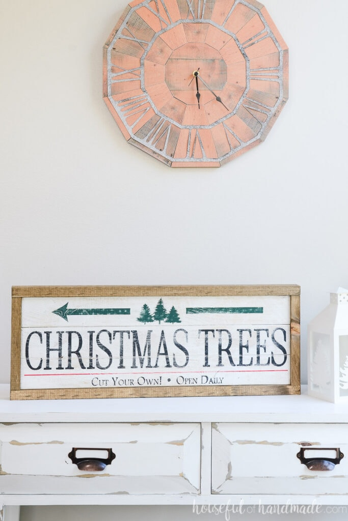 Christmas tree farm side of the double sided wood sign sitting on a white console table under a rustic wall clock.