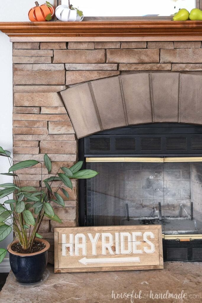 Neutral hayrides side of the double sided wood sign on a fireplace hearth next to a plant.