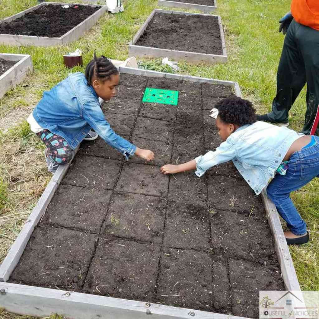 Children helping with planting a garden bed.
