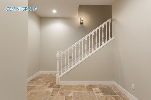Basement home tile floor hallway leading up to staircase.