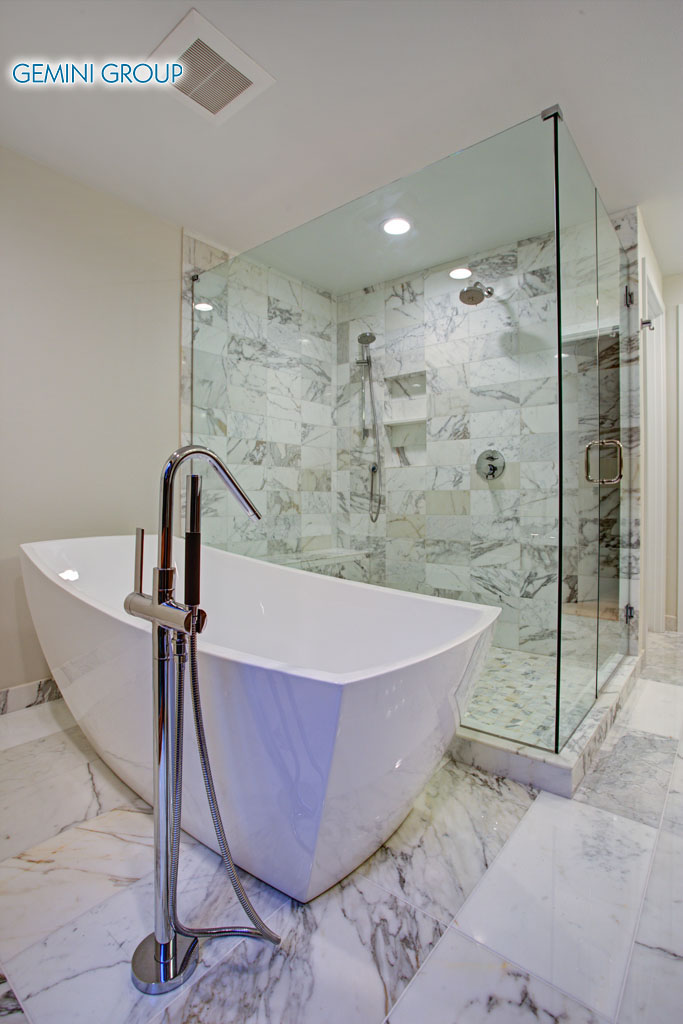 Sleek bathroom features freestanding bathtub paired with floor-mounted faucet atop marble floor placed in front of glass shower accented with rain shower head and gray marble surround.