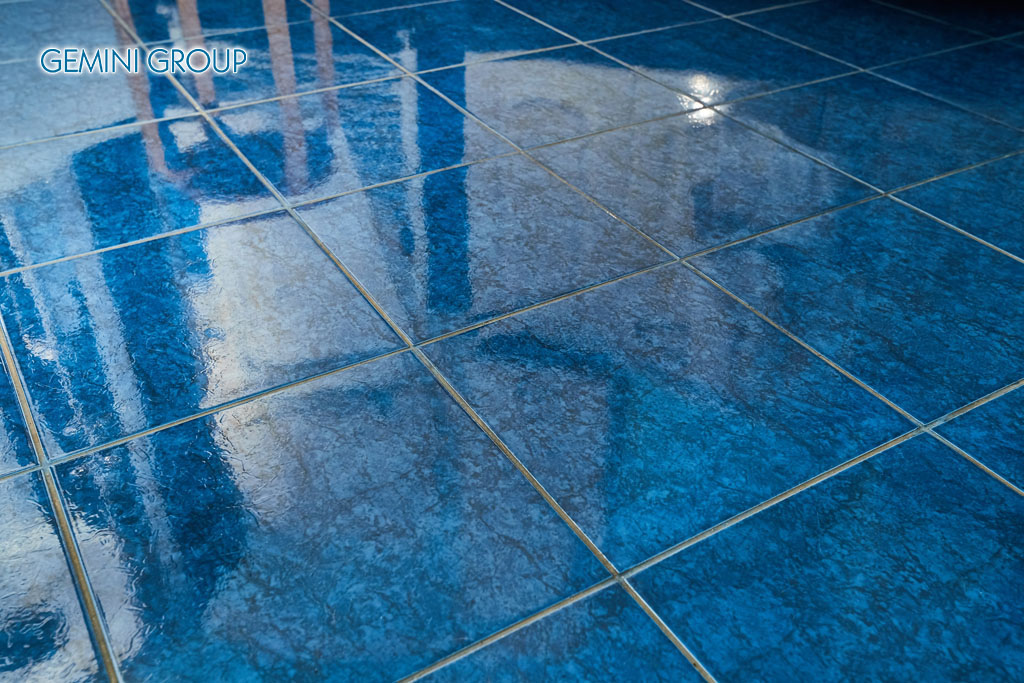 Shiny blue tiled bathroom floor reflecting light