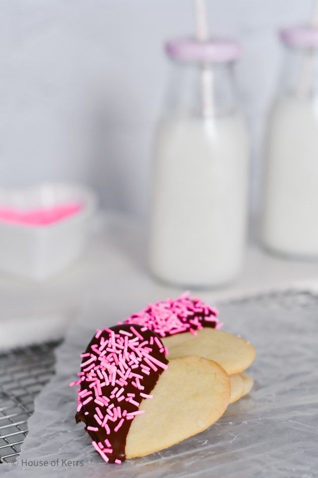 chocolate dipped heart cookies with pink sprinkles foodtography milk bottles in background close up shot