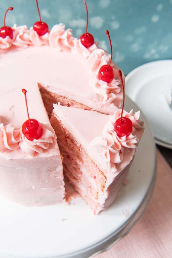 This homemade Vintage Cherry Chip Layer Cake made from scratch is bursting with sweet cherry flavor and tinted the perfect shade of pink from nothing other than the maraschino cherry juice from the jar! Chopped up maraschino cherries are folded into the batter to make sure the cherry flavor really comes through in this super fun, moist Cherry Chip Layer Cake that is perfect for almost any celebration, but especially Valentine's Day!