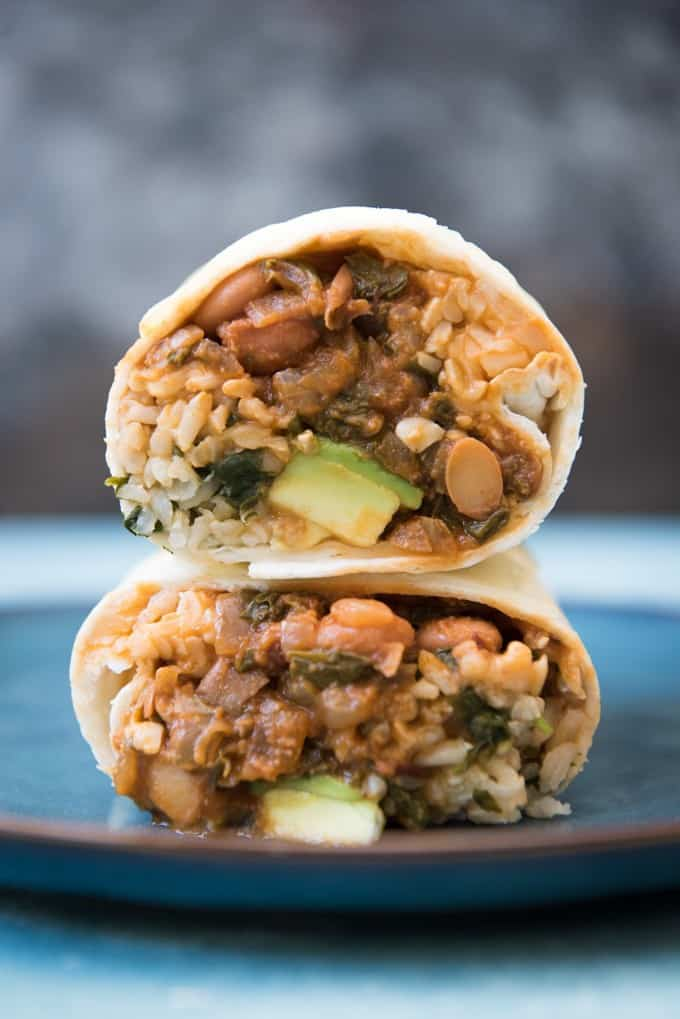These Vegetarian Swiss Chard and Pinto Bean Burritos are the ultimate in meatless meal Tex-Mex comfort food. Stuffed with brown cilantro rice, lots of melty cheese, diced avocado, and a smokey chipotle swiss chard and pinto bean filling, they are super satisfying for even the most avowed meat-eaters!