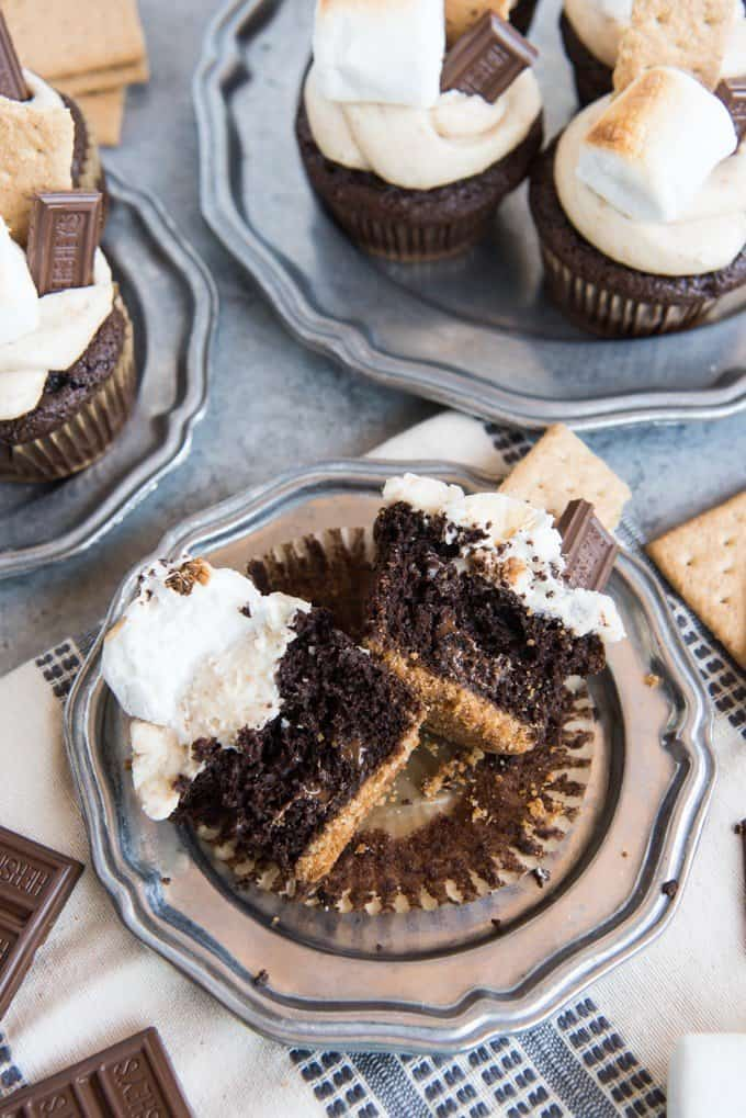 These S'mores Cupcakes with Graham Cracker Frosting, Toasted Marshmallows, and Hershey's Chocolate are the best ever!  Topped with a uniquely wonderful graham cracker cream cheese frosting, toasted marshmallows, extra Hershey's chocolate bar and pieces of graham cracker, these S'mores Cupcakes with Graham Cracker Frosting bring back memories of summertime, camping, and campfires in all of us!
