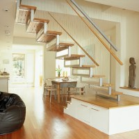 Living/dining room with wooden floor and bespoke staircase ...