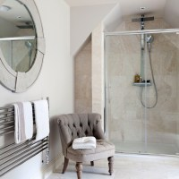 Classic en-suite bathroom with travertine tiles ...