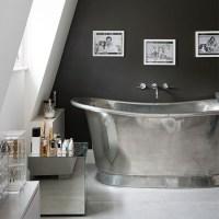 Streamlined attic bathroom with silver roll-top bath ...