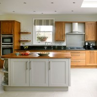 Traditional kitchen with painted grey and plain wood units ...