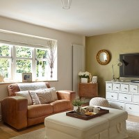 Neutral living room with white and leather furniture ...