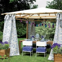 Garden gazebo with blue floral curtains and paper lanterns ...