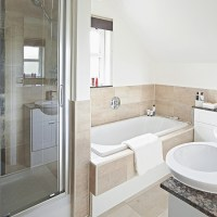 White bathroom with neutral tile bath panel and ...