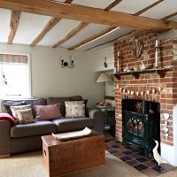 Country living room with wooden beams and exposed brick ...