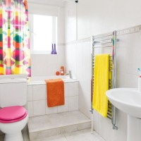 White bathroom with pink yellow and orange accessories ...