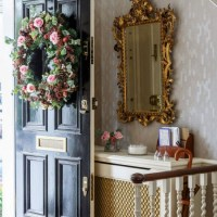 Traditional hallway with black front door and floral ...